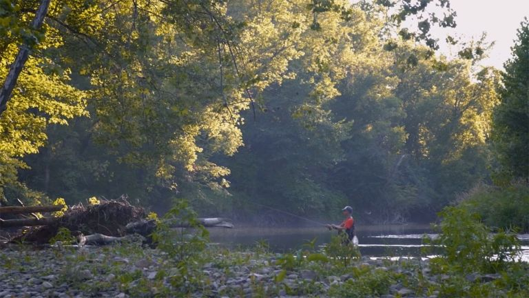 Steve Bolich, dressed in waders and a red shirt stands in the middle of stream fly fishing.
