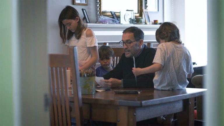 Darin Jensen sits at his wooden dining room table surrounded by his three young kids.