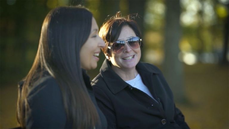 Megan Torres and her mother, Michelle, share a laugh on a park bench.