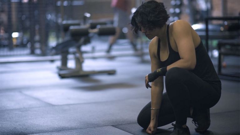 Zee Wolters in black tank top and workout tights kneels on one knee as she takes a break from lifting weights at the gym.