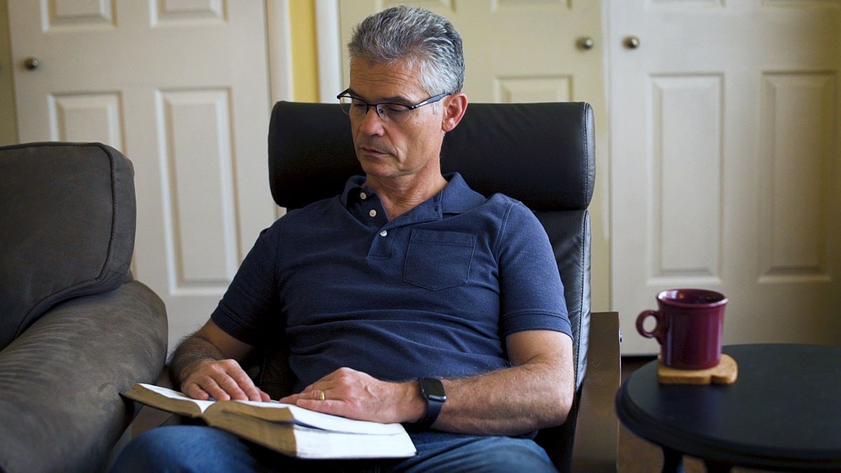 Steve Bolich sits in a leather reclining chair reading a book.