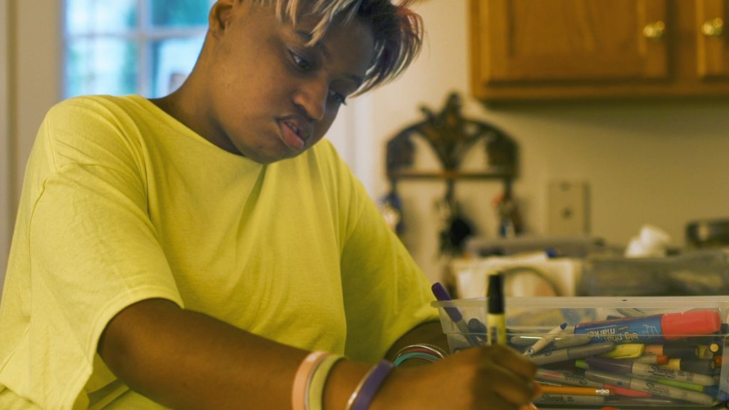 Anise Saunders sits at her kitchen table drawing with a box full of Sharpie markers next to her.
