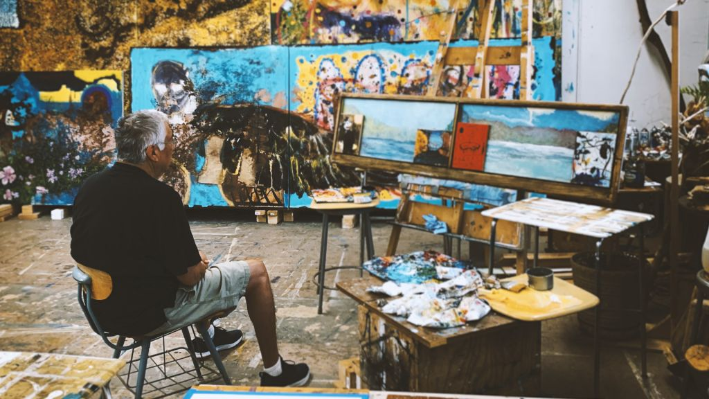 Jay Carrier sits in a chair in his art studio surrounded by large format paintings