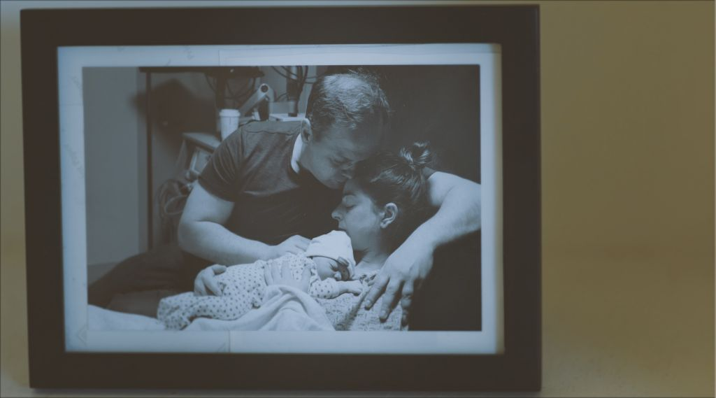 An old black and white photo of Jenn and Nic Hepton in the hospital. Nic is leaning over Jenn as she holds their stilborn daughter, Loey