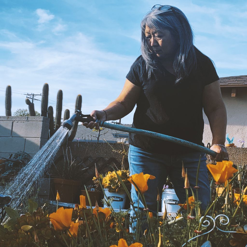 Jayne Agena holds a hose watering a planter box full of yellow flowers.