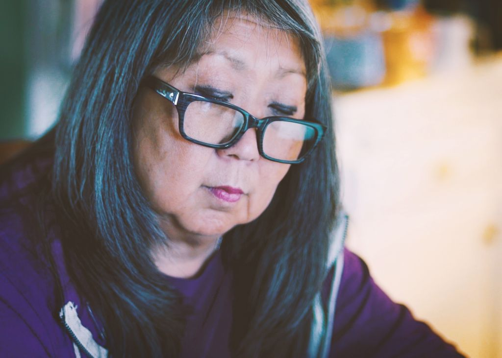 Jayne Agena in a purple sweatshirt and wearing reading glasses reads a book