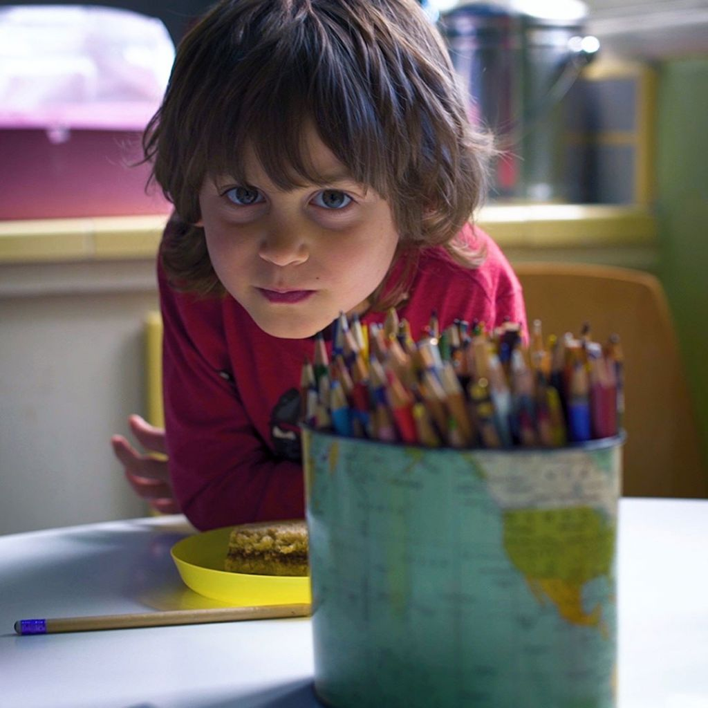 Close up of a young kid eating a snack with a jar full of many colored pencils in the foreground.
