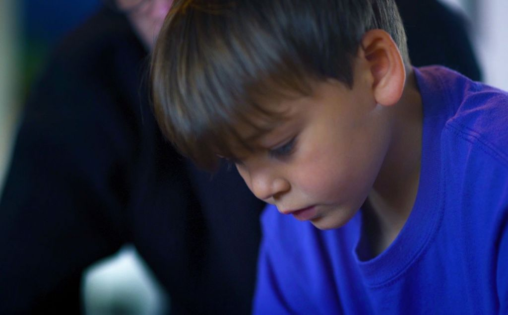 Close up of a young boy in a blue tshirt reading.