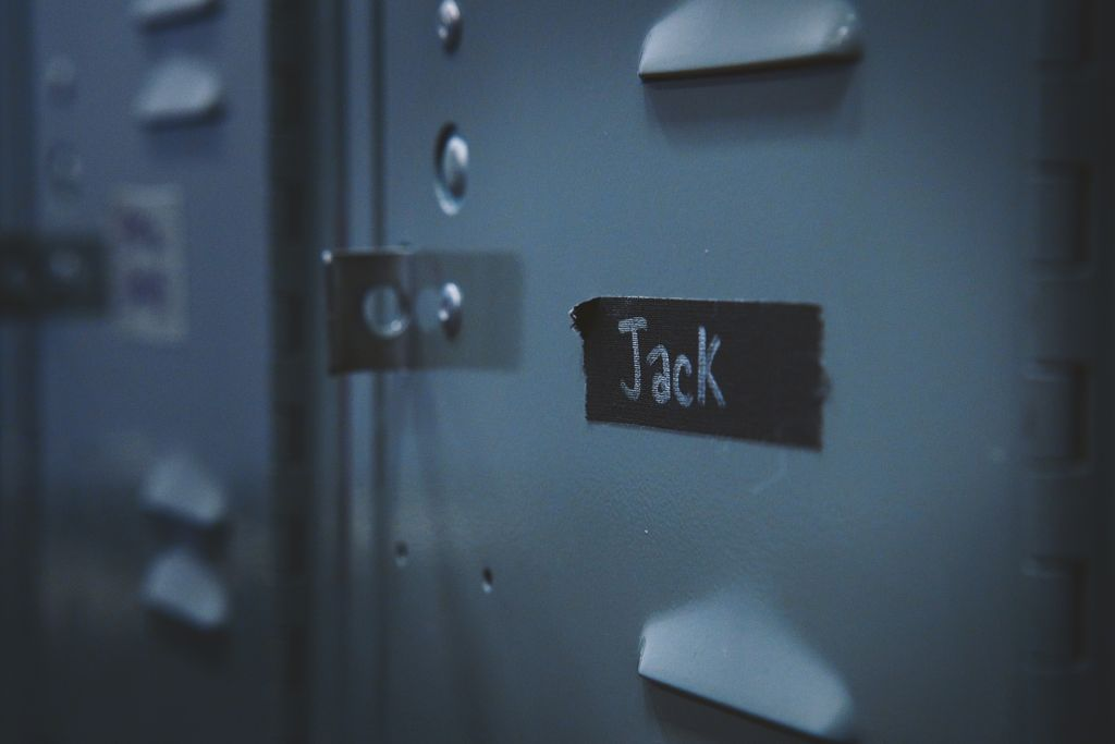 A high-contrast photo in gray and black of a locker with a piece of tape on it labeled Jack