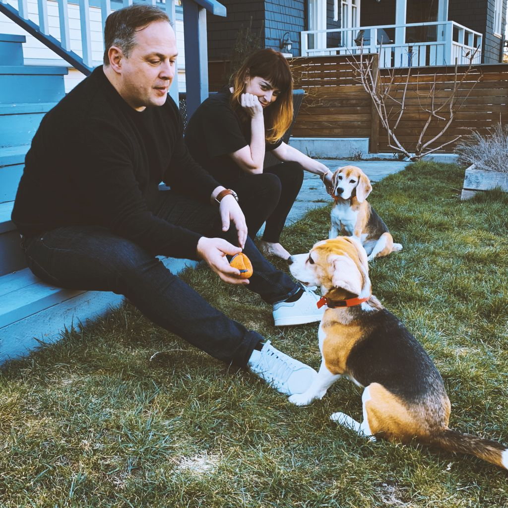 Jenn and Nic Hepton sit on their porch stairs with two dogs