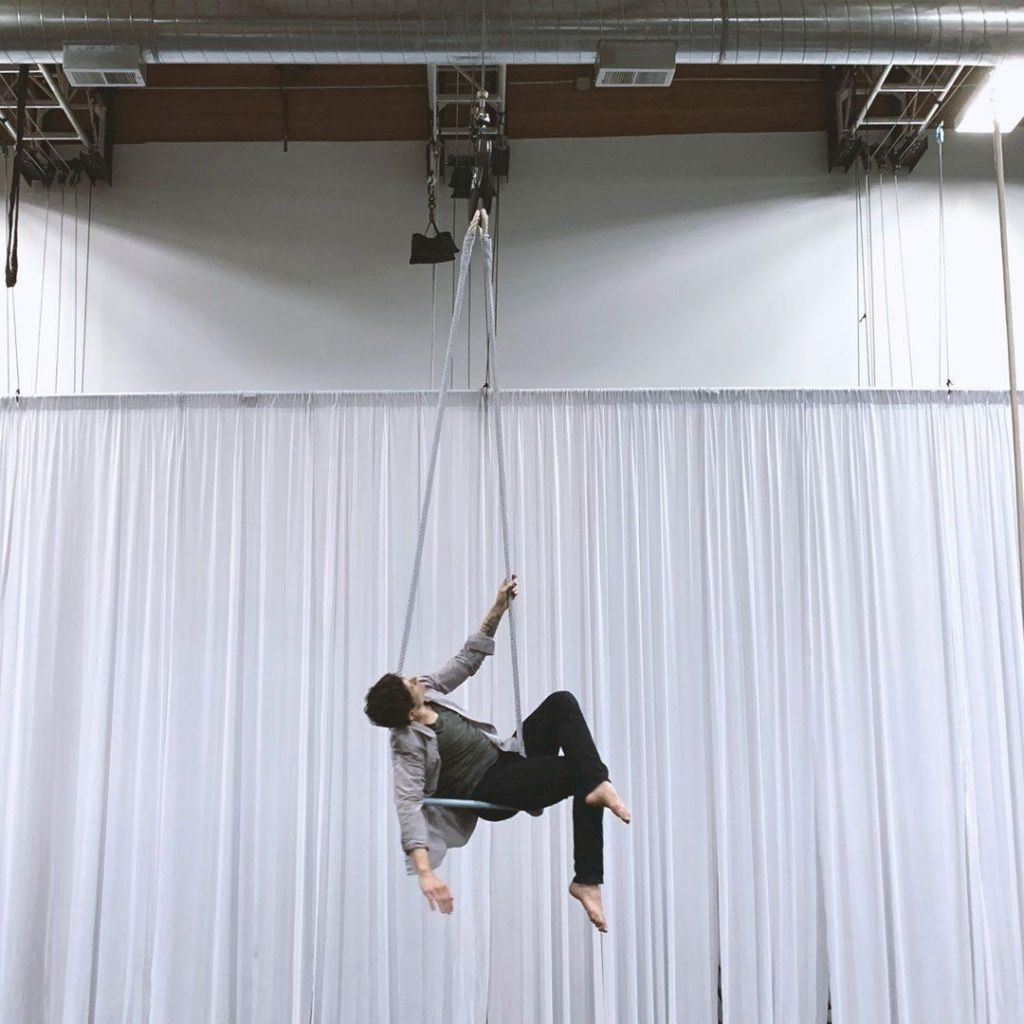 Jack StockLynn hangs from a trapeze in front of a white curtain