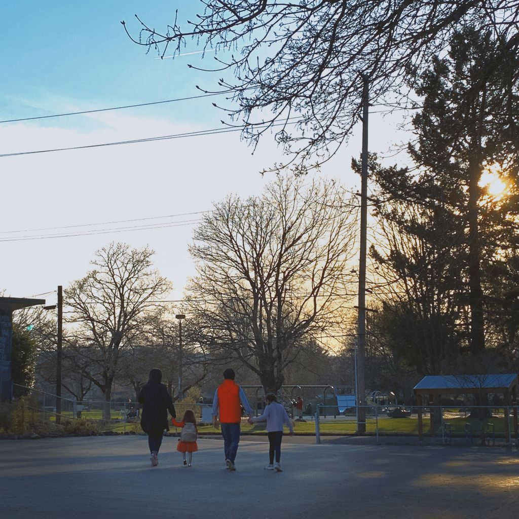 The Suddes Hilliard family strolls through a park at dusk as the sun sets between trees
